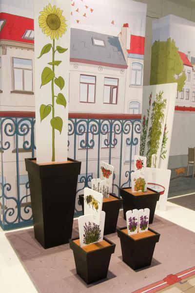 """Devant le panneau représentant un balcon de ville, se trouvent des pots dans lesquels les enfants ont """"planté"""" les représentations des plantes choisies, surmontées des dessins des animaux qui en profiteront le plus."""