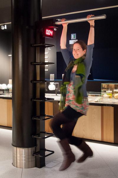 Een bezoeker test de kracht van haar armen door zo lang mogelijk aan een staaf te hangen (foto: Thierry Hubin - KBIN)