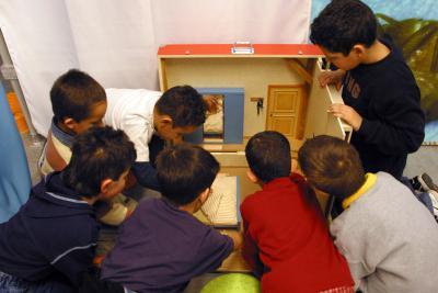 Kinderen rond een maquette van een kamer