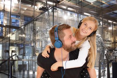 Une fille et son père visitent la Galerie des Dinosaures en écoutant le podcast Be My Guide (image : IRSNB)