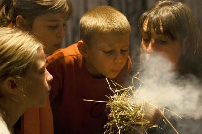 """Un groupe de visiteurs en train de faire du feu """"à la préhistorique"""" (photo : Koen Broos)"""