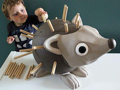 Un jeune enfant replace des piquants en bois sur un hérisson géant