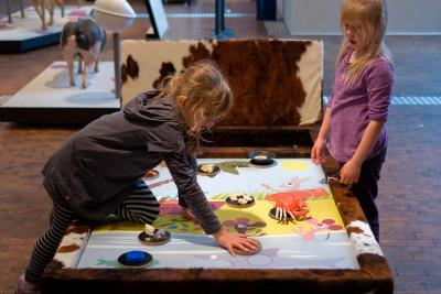 Children trying to match several materials with their owners on a picture