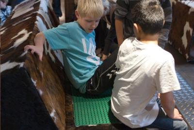 Kinderen zitten op verschillende materialen (waarvan een met pinnen)