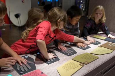 Kinderen proberen verschillende temperaturen met de handen evalueren