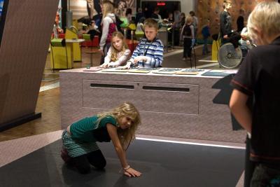 Kind proberend verschillen van de temperatuur op een speciale vloer te  voelen