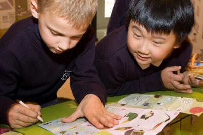 Een kind vult op zijn folder het deel over het voeren in.