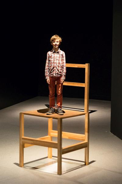 A boy seems to stand on a giant chair.