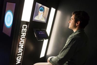 Cabine dans laquelle un visiteur observe  l'anatomie générale de son cerveau en 3D