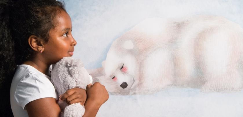een jonge bezoeker en haar teddybeer voor de tekening van een slapende ijsbeer in de tentoonstelling Teddy en Beer (foto: Thierry Hubin / KBIN)