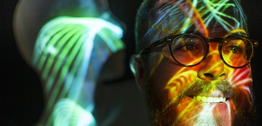 Visiteur à côté d'une projection sur un mannequin grandeur nature (photo: Koen Broos)