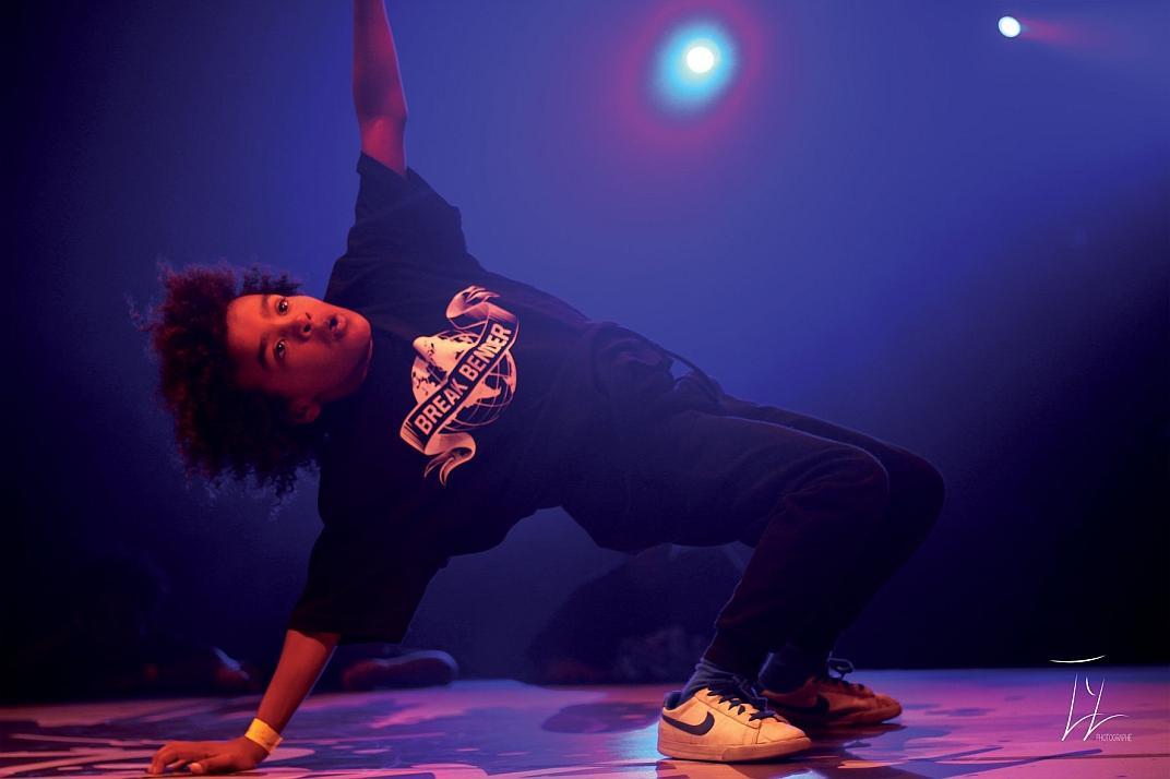 un jeune break dancer du groupe Break Bender en pleine figure au sol