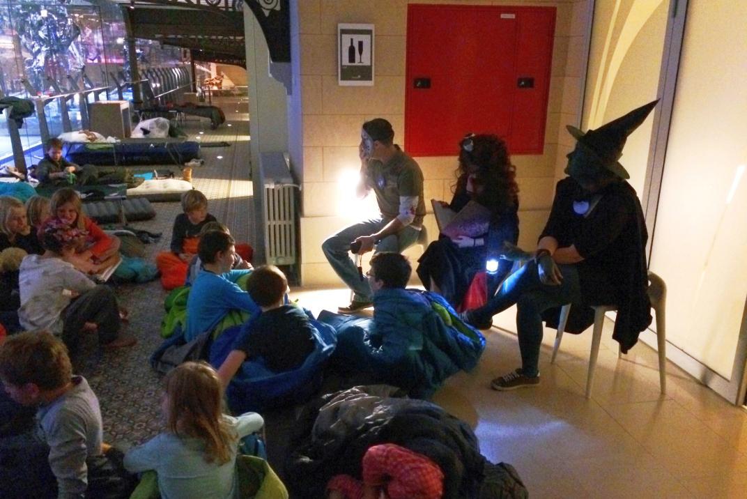 Les enfants sont rassemblés autour des animateurs pour écouter l'histoire qui fait peur