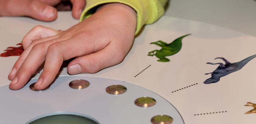 Een kind verbindt twee beelden op een elektrospel in de Galerij van de Dinosauriërs