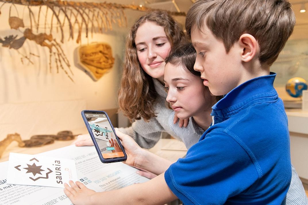 Une fratrie répond ensemble aux questions posées par l'app Sauria dans la salle des Mosasaures (photo : Thierry Hubin / IRSNB)