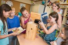 Des écoliers placent la caméra connectée dans le nichoir du kit XperirBIRD.be (photo : IRSNB)