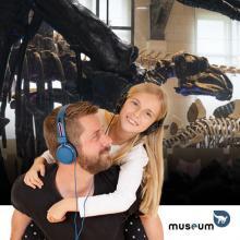 Vader en dochter in Dinogalerij, naar audioguide aan het luisteren met koptelefoon op.