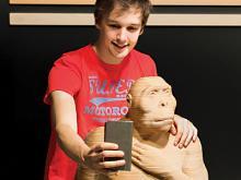 Een jonge bezoeker maakt een selfie achter een Paranthropus boisei (foto: Thierry Hubin, KBIN)