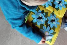 Een peuter bekijkt een boek over kriebelbeestjes tijdens een Atelier voor de Allerkleinsten (foto: Coralie Boeykens / KBIN)