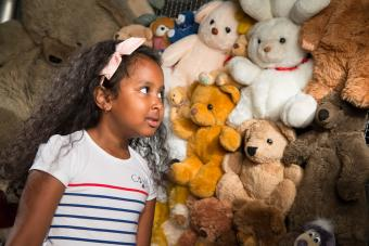 child in front of a wall of teddy bears © KBIN / IRSNB / RBINS